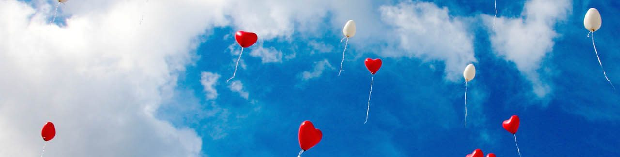 Blue sky with heart balloons