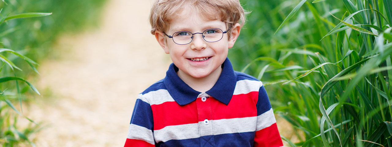 Boy Smiling in Grass, wearing glasses in Ellicott City