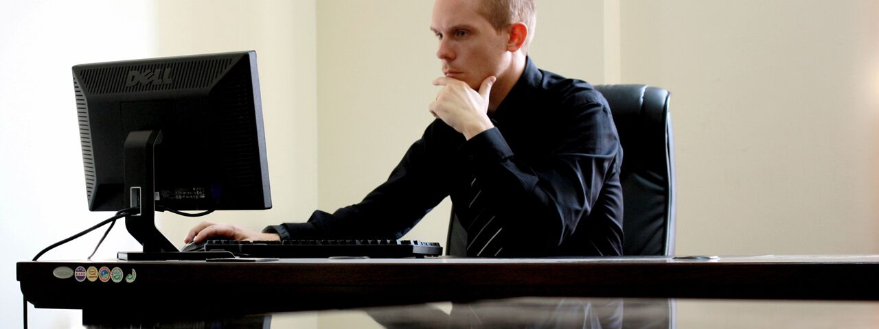 Concerned Business Man at Desk with Computer