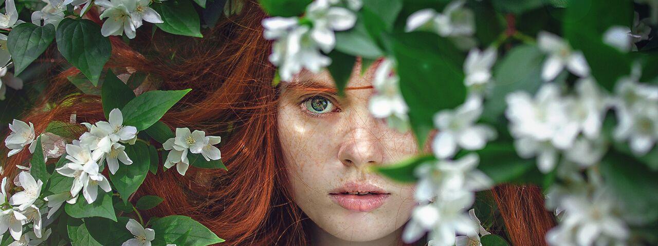 Green-eyed girl looking through flowers