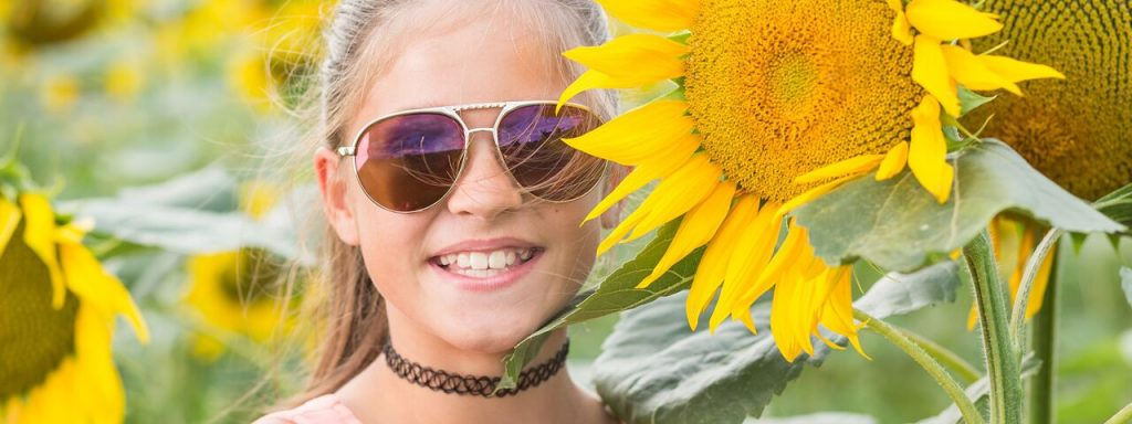 Girl wearing sunglasses surrounded by sunflowers in Fort Worth, Texas