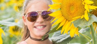 Girl with sunglasses next to a Sunflower, Optometrist, Fayetteville, Burlington, Wilmington, NC