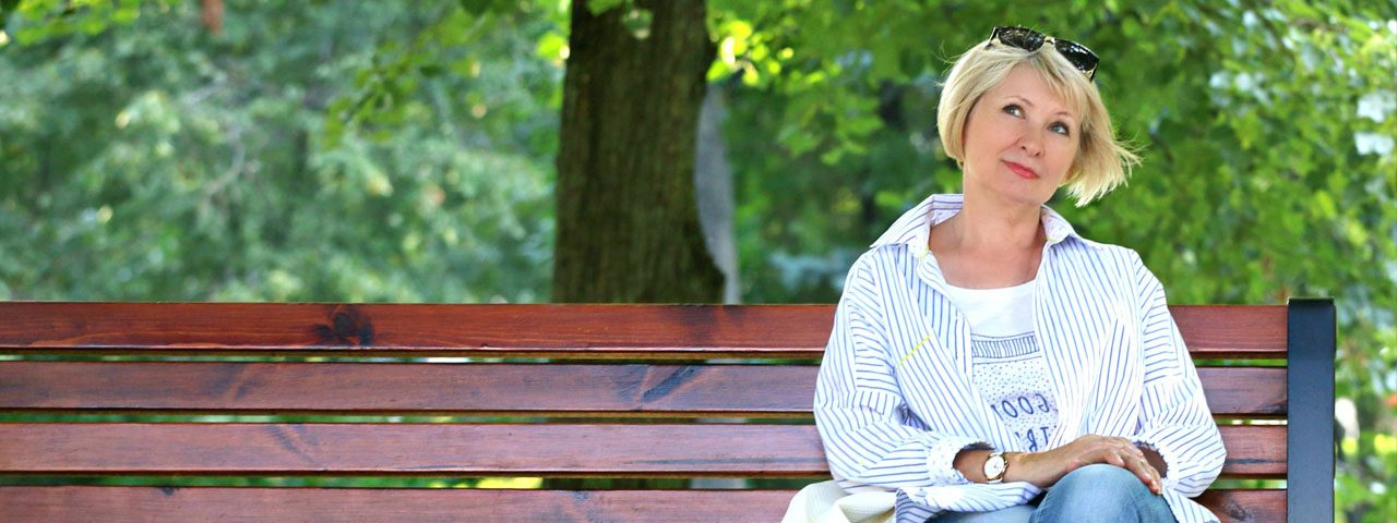 Elderly Woman sitting on bench in park