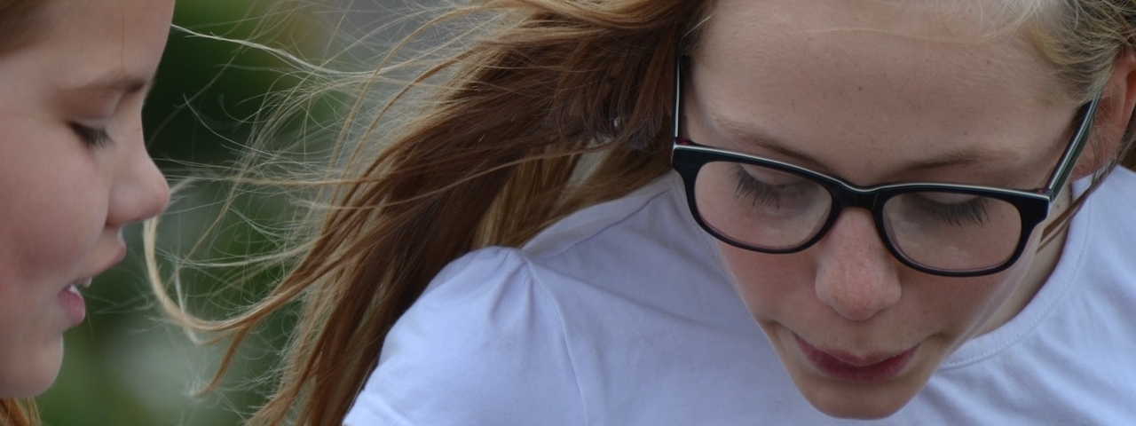 girl with white shirt, wearing glasses looking down, in Lakeville, MN