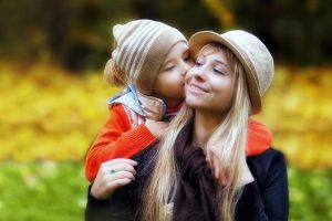 Child Kissing Mother Outdoors 1280×853