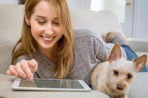 Woman, after eye exam, enjoying iPad, next to dog