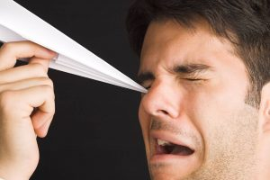 man poking eye with paper airplane - Emergency Eye Care Services in Greer and Boiling Springs, SC