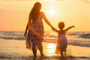 Bergen County eye doctor | mother and child holding hands in the sunset