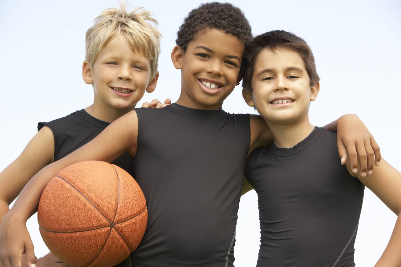 3 boys holding a basketball