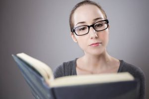 woman with black glasses reading a book