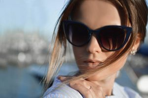 woman sunglasses hair blowing | Eye Care Optics in Burlington, MA