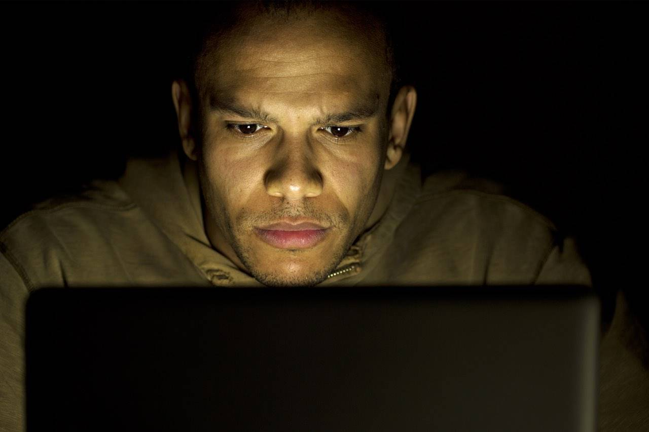 black guy looking at computer screen to advertise dangers of blue light