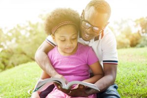 Father (wearing eyeglasses) and Daughter, reading a book