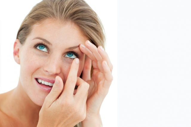Woman blonde putting in contact lens