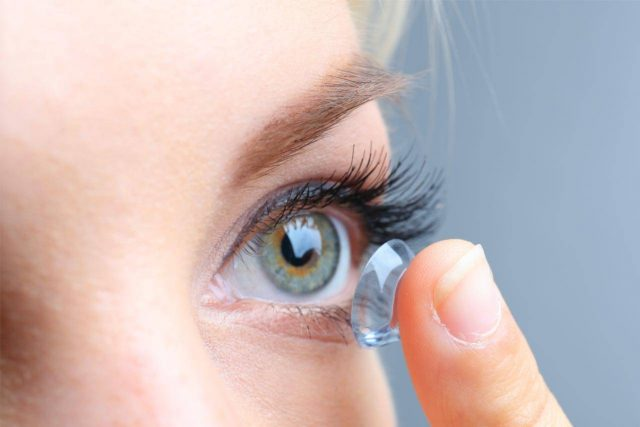 close up on woman with blue green eyes putting in contacts
