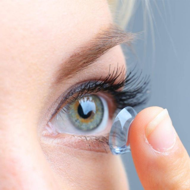 close up woman putting contact lenses in her blue green eyes