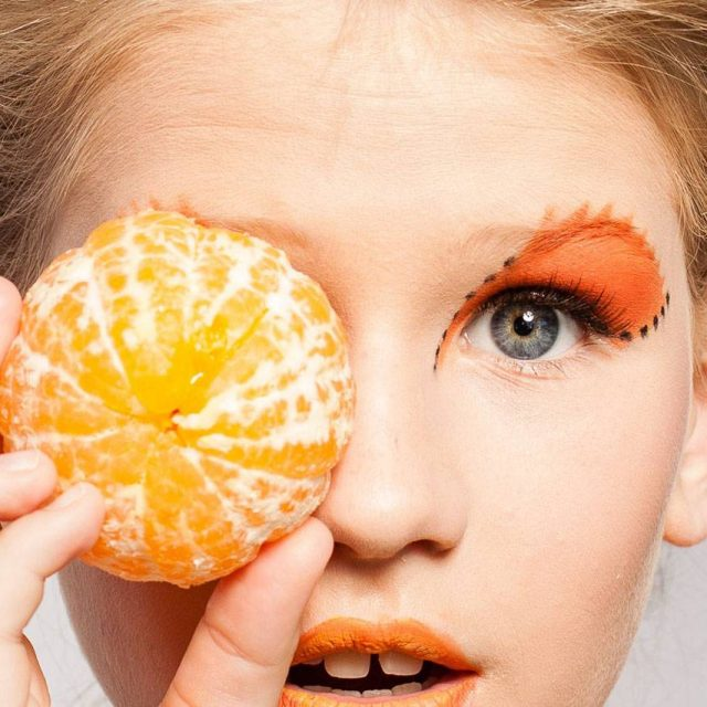 woman holding orange next to her orange shadowed eyes and near orange lips to advertise eye nutrition