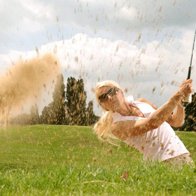 Woman golfing and wearing sports glasses, in Harrisburg