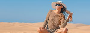 woman sunglasses hat sitting beach | Spectacle Eye Design in Austin, TX