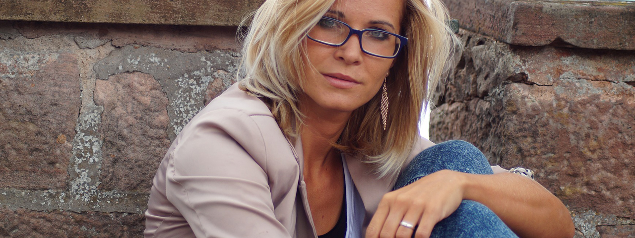 Woman with glasses sitting by wall 1280x480