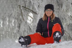 Woman with glasses sitting in snow 1280×853