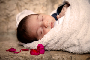 baby swaddled in white with flower petals