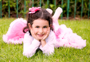 girl with pink bow in the grass