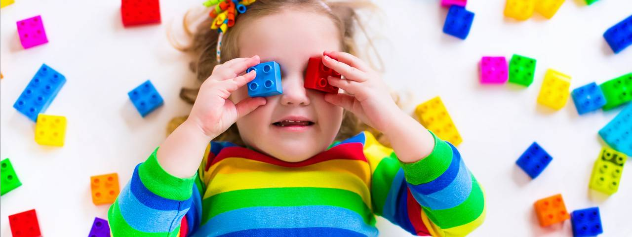 little girl wearing rainbow shirt putting bright colored blocks over her eyes