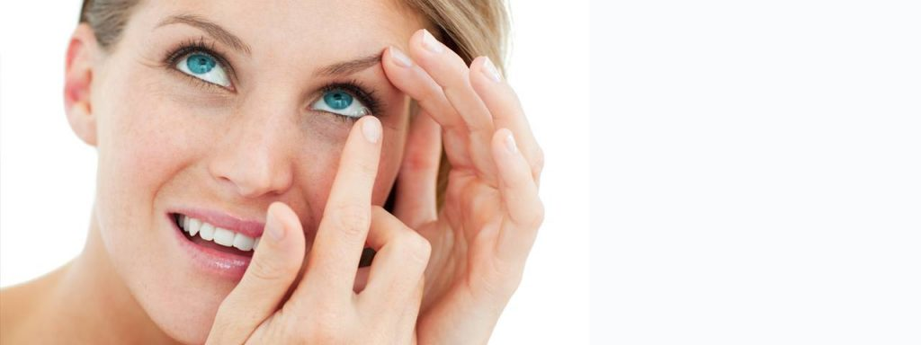 attractive blond woman putting in contact lens- eye doctor - Piscataway & Edison, NJ