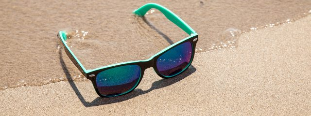 blue sunglasses sandy beach 1280x480