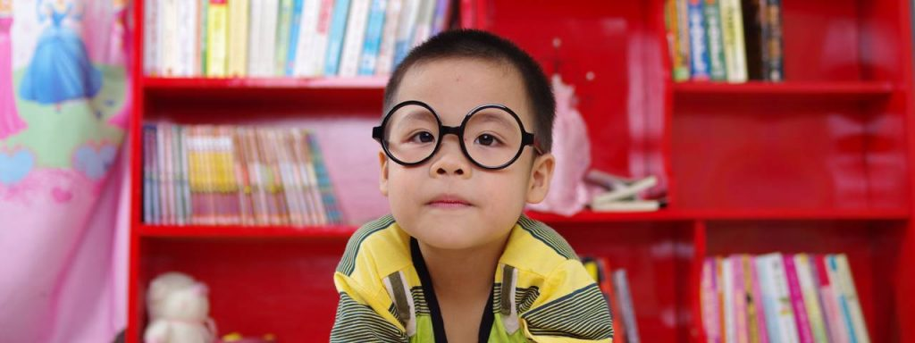 boy in front of red bookcase - eye care - optometrist - Chula Vista, CA