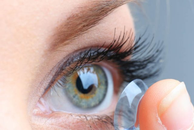 close up of a blue eyed female putting in contact lenses