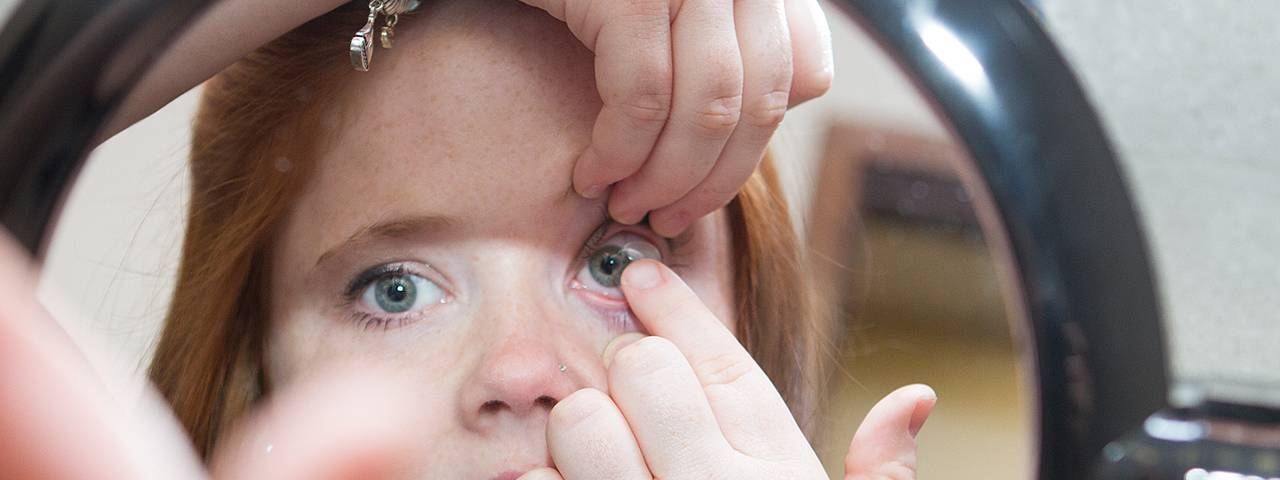 Girl inserting scleral contact lens