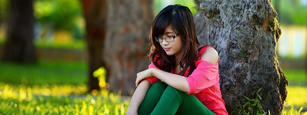 girl with glasses sitting under a tree in Austin, Texas