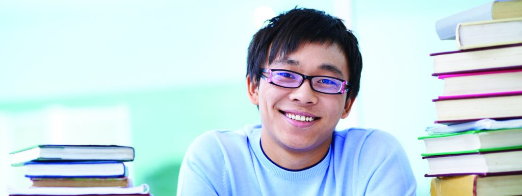 Boy with glasses surrounded by books, eye doctor, eye care, Fort Myers, FL