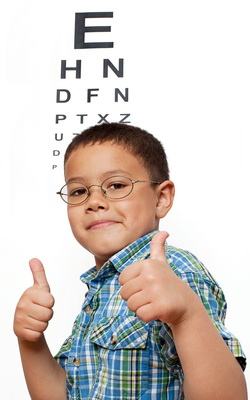 Boy wearing eyeglasses, giving thumbs up in front of eye chart