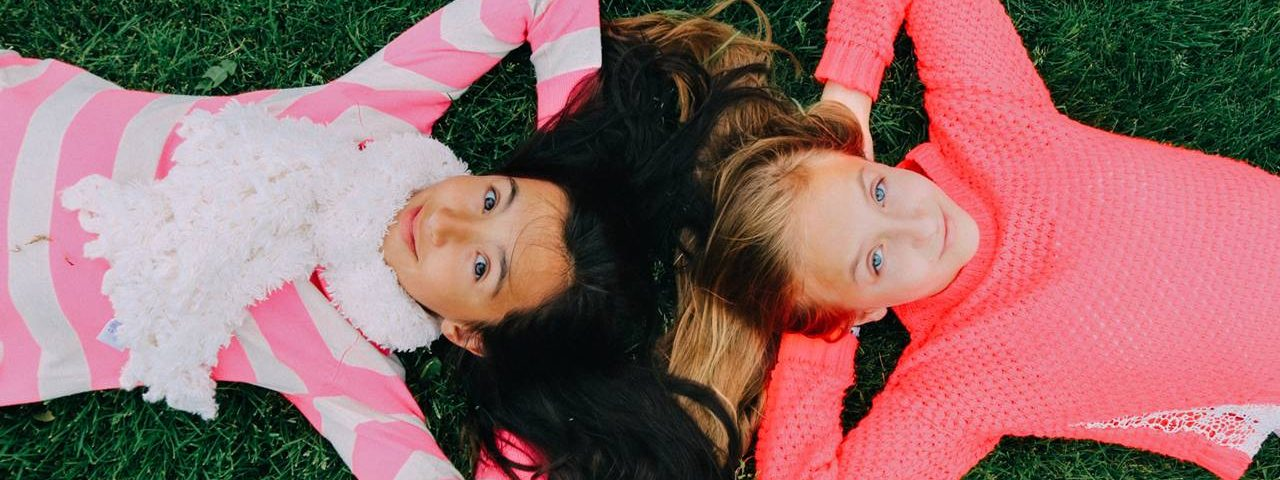 Young Girls Laying on Grass 1280x853 1280x480