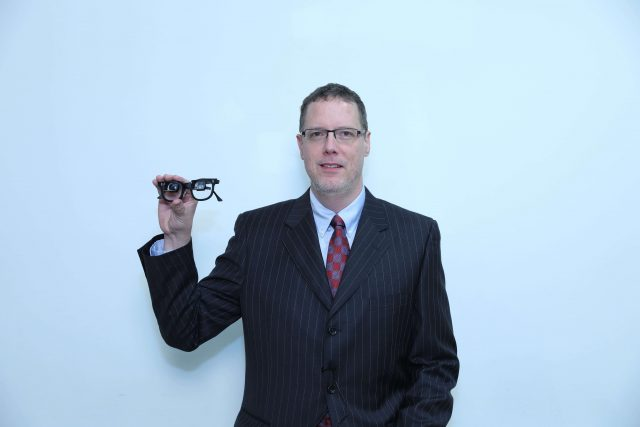 Dr. Cusic holding a pair of low vision glasses