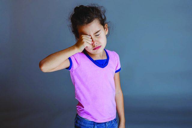 Optometrist, little asian girl rubbing her eyes in Astoria, New York