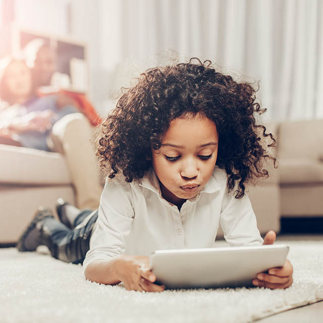 Thoughtful Kid Looking At Tablet While Resting On Soft Tapis Ins