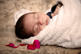 baby swaddled in white with fl 325×217