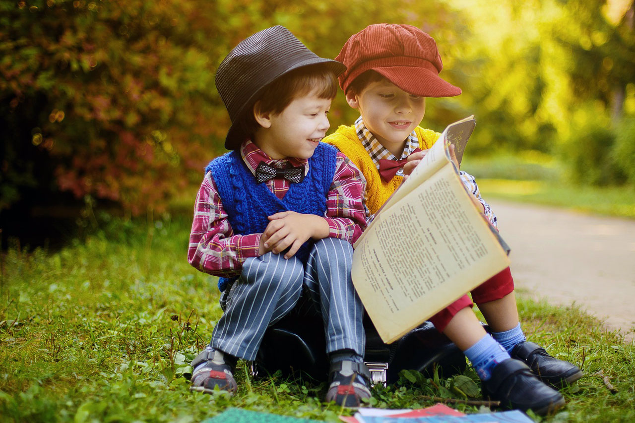 Children Reading Newspaper Outside 1280x853