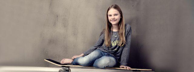 Eye doctor, teenage girl sitting on a skateboard in Raleigh, Durham, Cary, Fayetteville, Wilmington & Burlington, NC