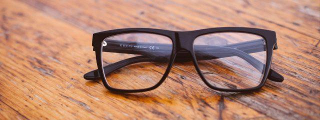 Eye doctor, pair of eyeglasses on wooden surface in Austin, TX