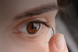 Girl with brown eyes inserting a contact lens in Lakeville Minnesota