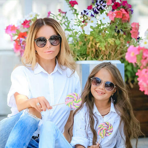 smiling mother and daughter wearing sunglasses