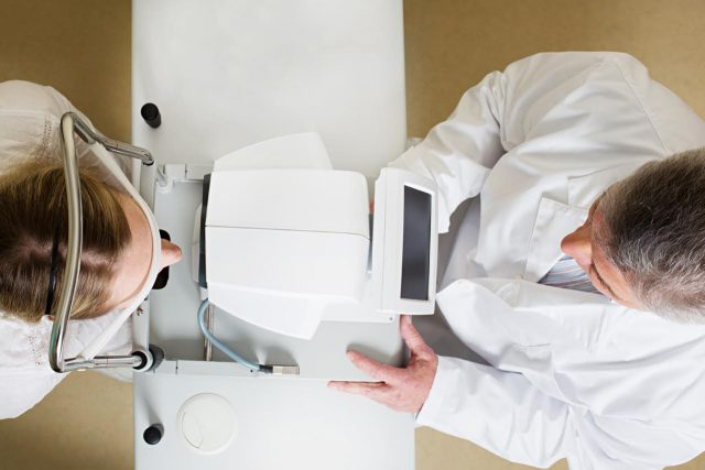 Doctor and Patient Using Phoropter for Eye Exam in Kyle, TX