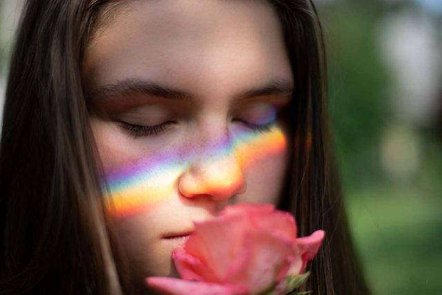 Girl closing eyes, smelling flower