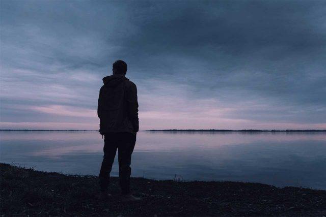 man alone by ocean thinking of treatment for keratoconus