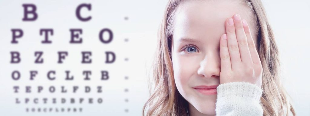 Girl in front of eye chart, eye doctor, Fort Collins, CO